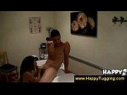An asian masseuse jerks her client off