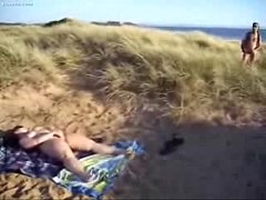 Horny slut loves to be watched while she masturbates at beach