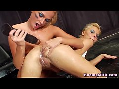 Squirting lesbians toy during enema session