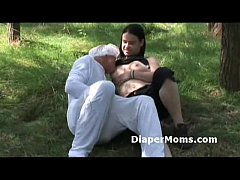 Brunette mom breast feeds adult baby in pajamas...