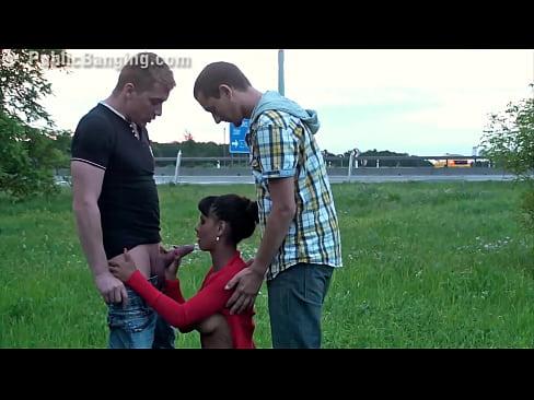 В общественном месте двое парней зажимают темнокожую девушку и дают ей минет